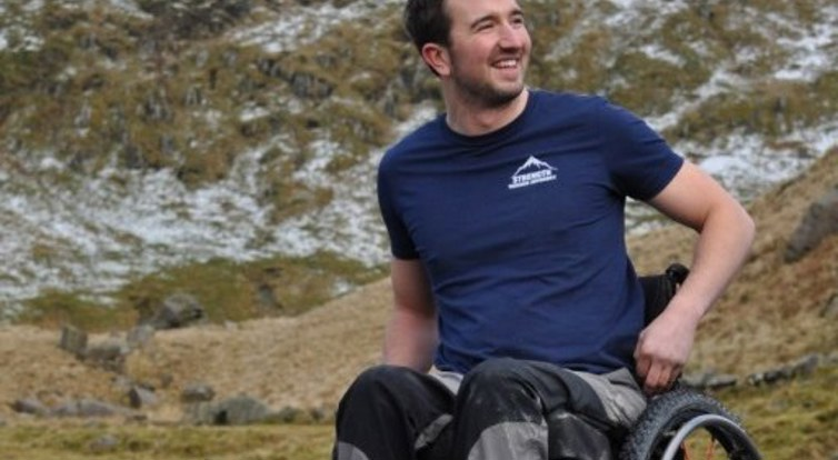 Darren Edwards in his wheelchair in front of a mountain
