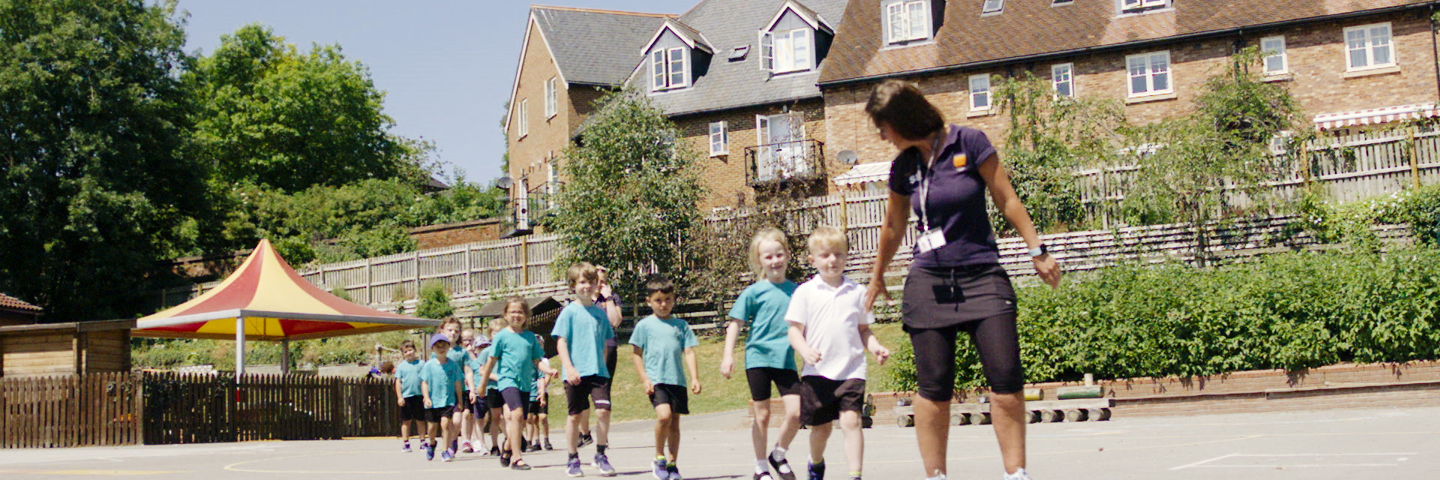 Children following teacher ready for a PE lesson