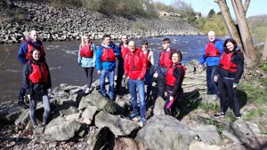 Pleydell Smith employees wearing life jackets standing on the edge of the river