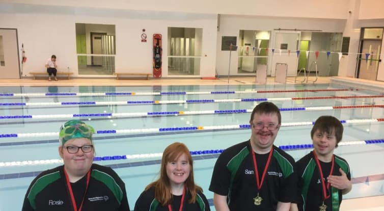 Four Special Olympic swimmers pictured standing in front of a swimming pool