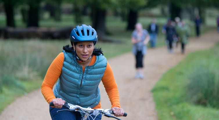 Lady cycling along path in a park