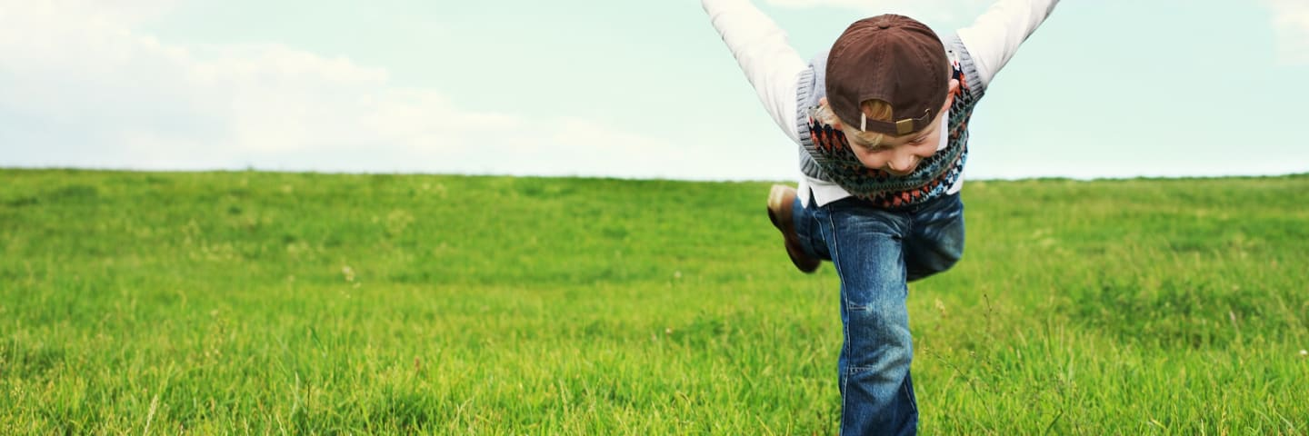Small boy excitedly running through a field