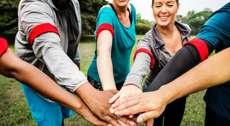 Volunteers all placing there hands together in the centre of a group