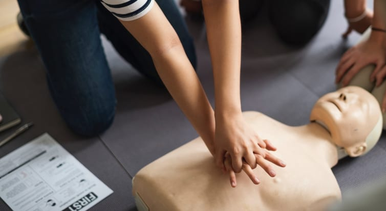 female performing CPR on a dummy