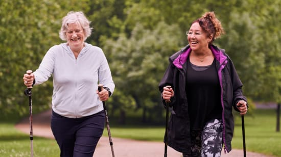 Two ladies nordic walking in a park