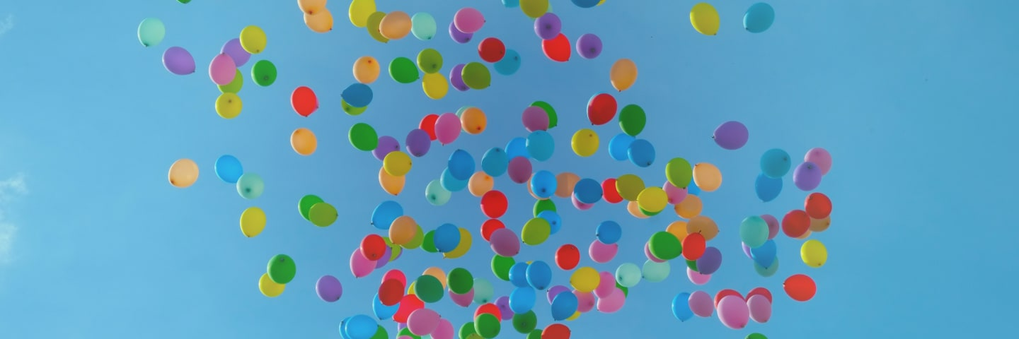 Balloons floating up into a bright blue sky
